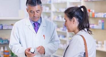 pharmacist and customer reviewing prescription