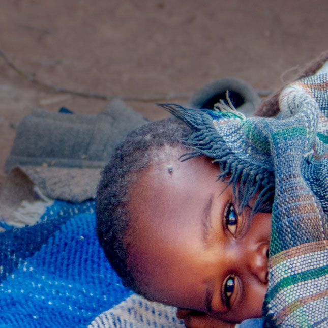 child peeking from under a blanket